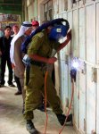 IDF officer from the military adminstration (DCL) blocking the shop of a Palestinian in the old city of Hebron. (Pic Credit ?)