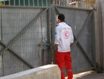 A Palestinian ambulance driver negotiates with the IDF in order to open the iron gate for him to pass in order to save the life of a Palestinian behind the closed gate. IDF officer from the military adminstration (DCL) blocking the shop of a Palestinian in the old city of Hebron. (Pic Credit ?)