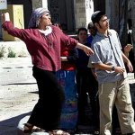 A criminal woman among the American pogroms throwing stons at the Palestinians
