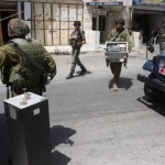 Israeli soldiers making off with stolen equipment from Radio FM 91.1 (Credit - Hebron journalists)